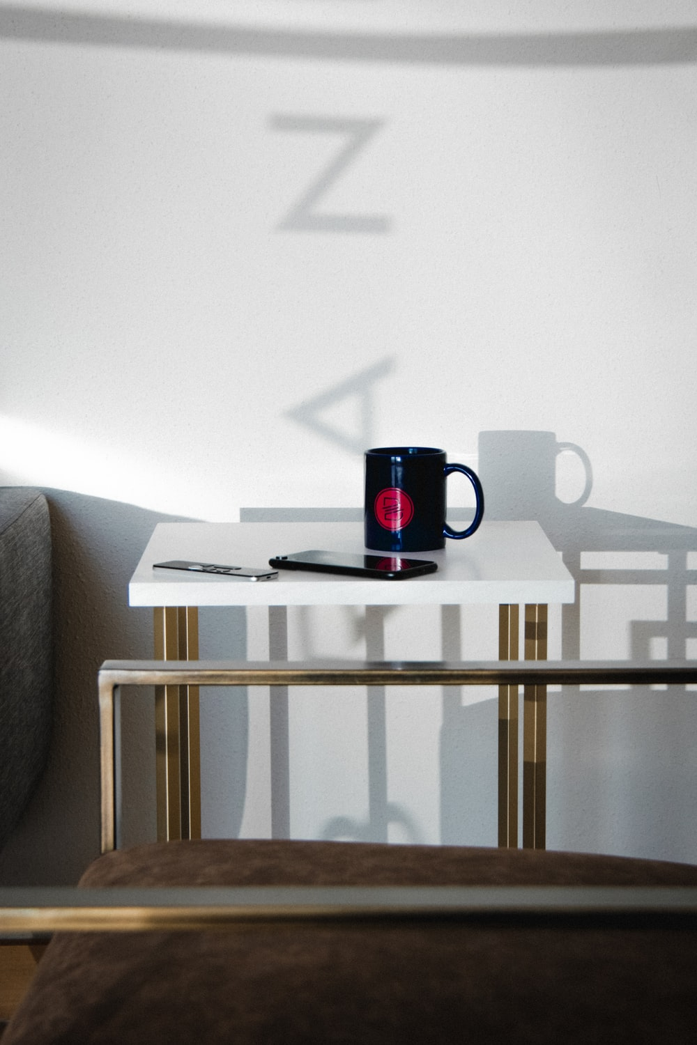 black and red ceramic mug on white wooden table