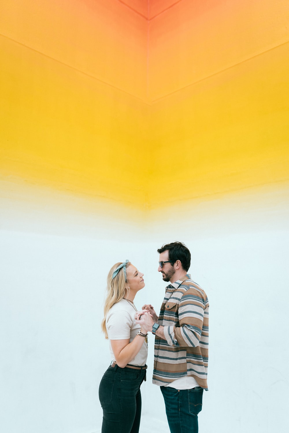 man and woman kissing beside yellow wall