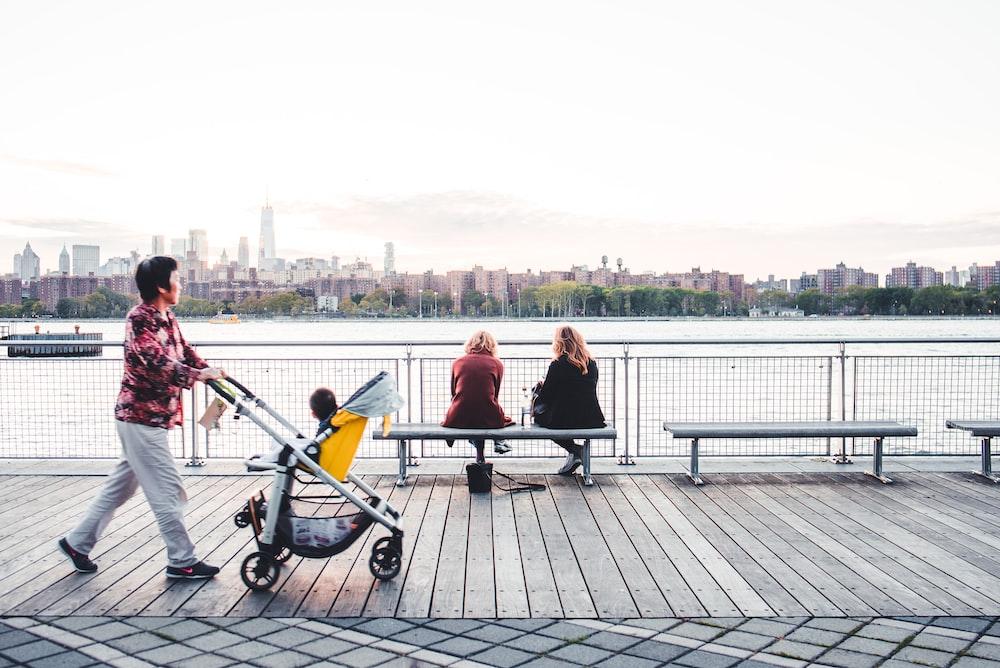 people sitting on black metal bench near body of water during daytime