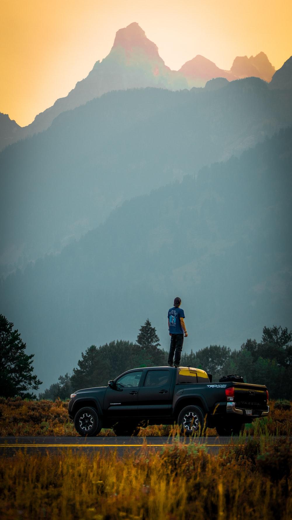man in black jacket standing on yellow car during daytime