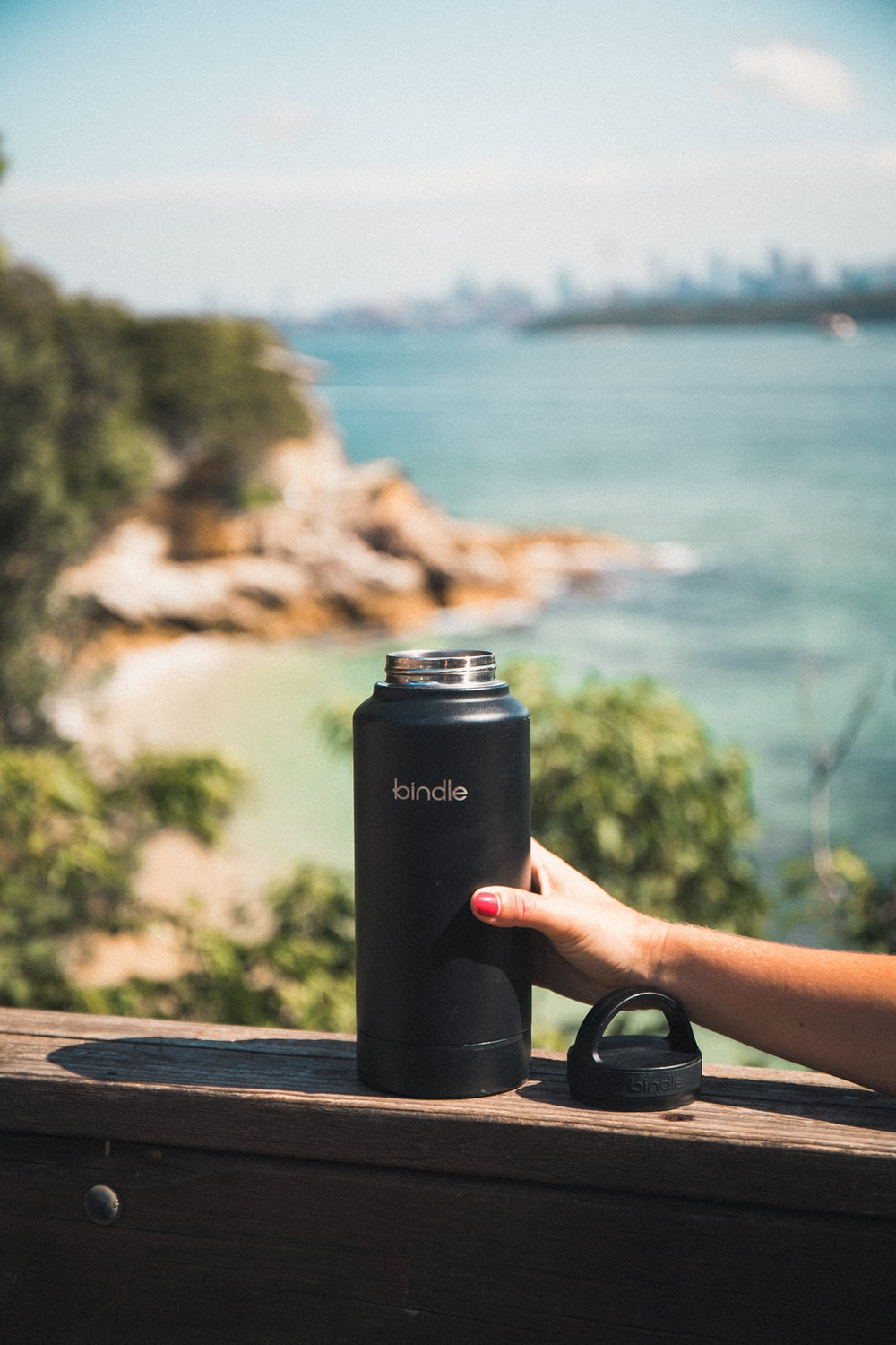 person holding black and silver tumbler