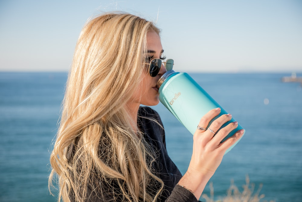 woman in black long sleeve shirt holding blue plastic bottle