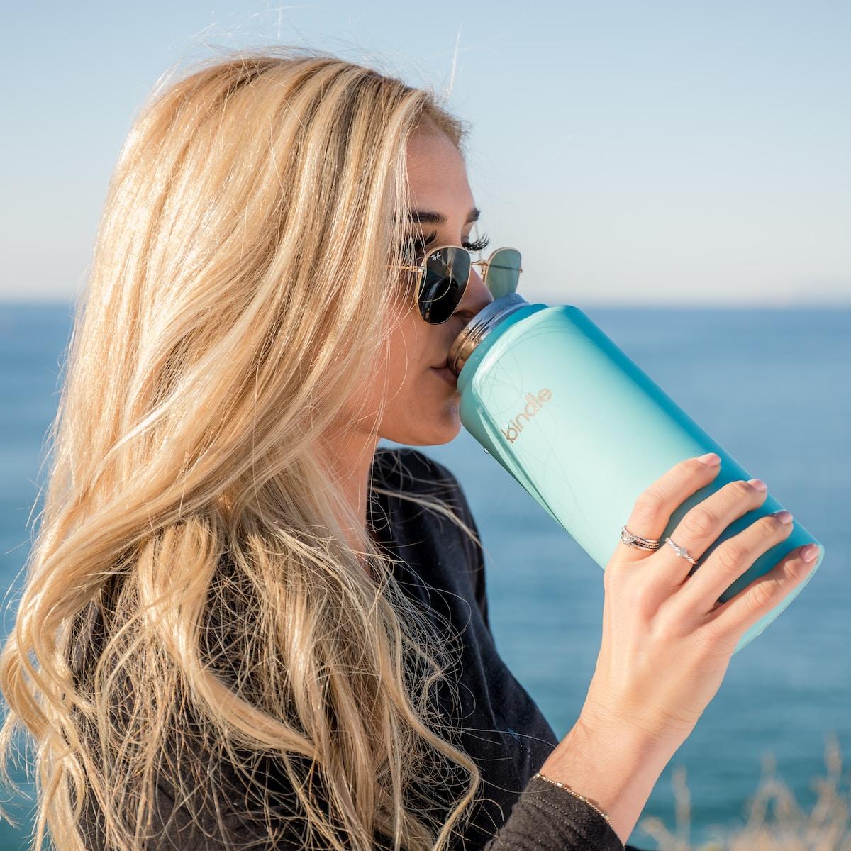 beber agua, vasos de agua, woman in black long sleeve shirt holding blue plastic bottle