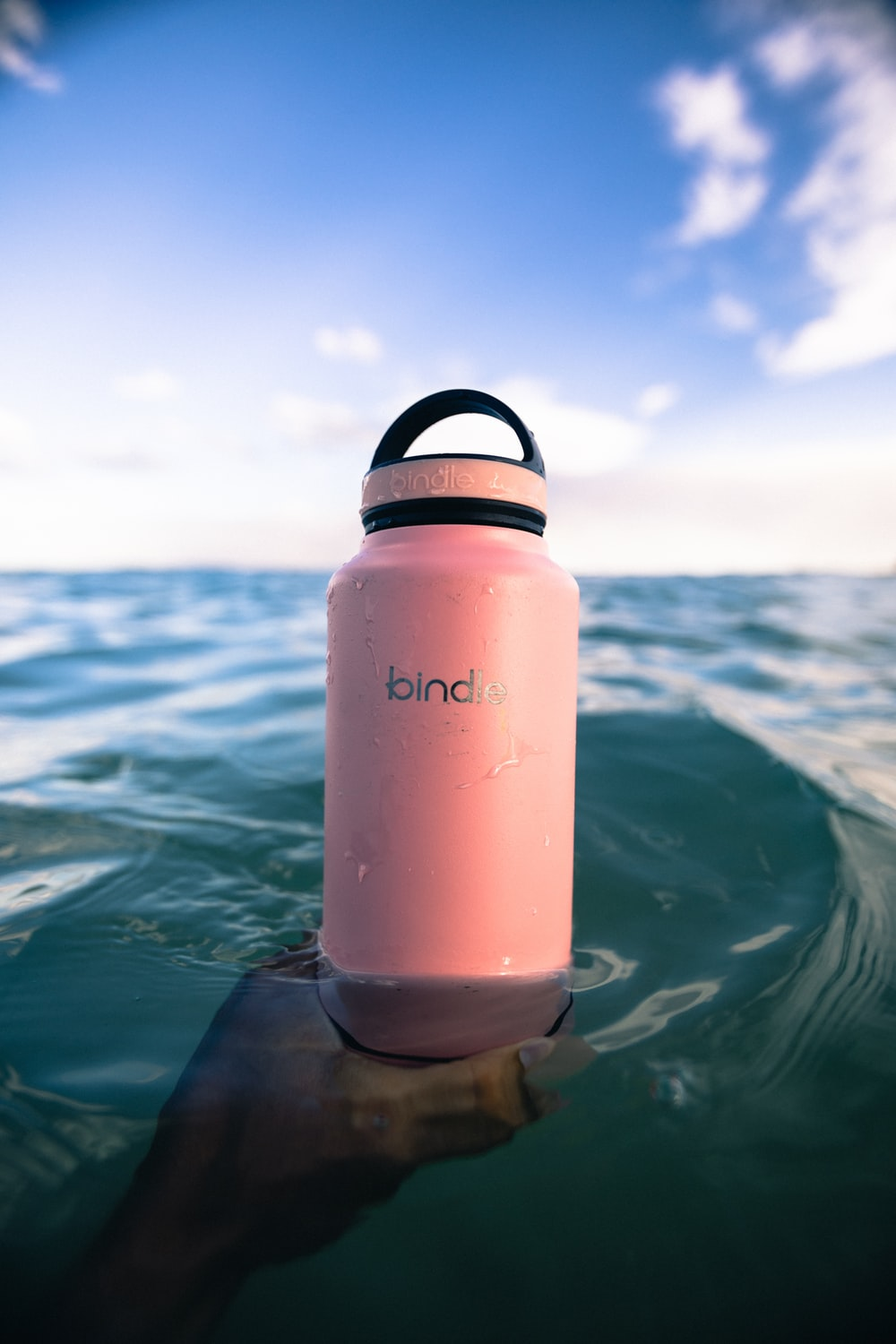 white and black plastic tumbler on water