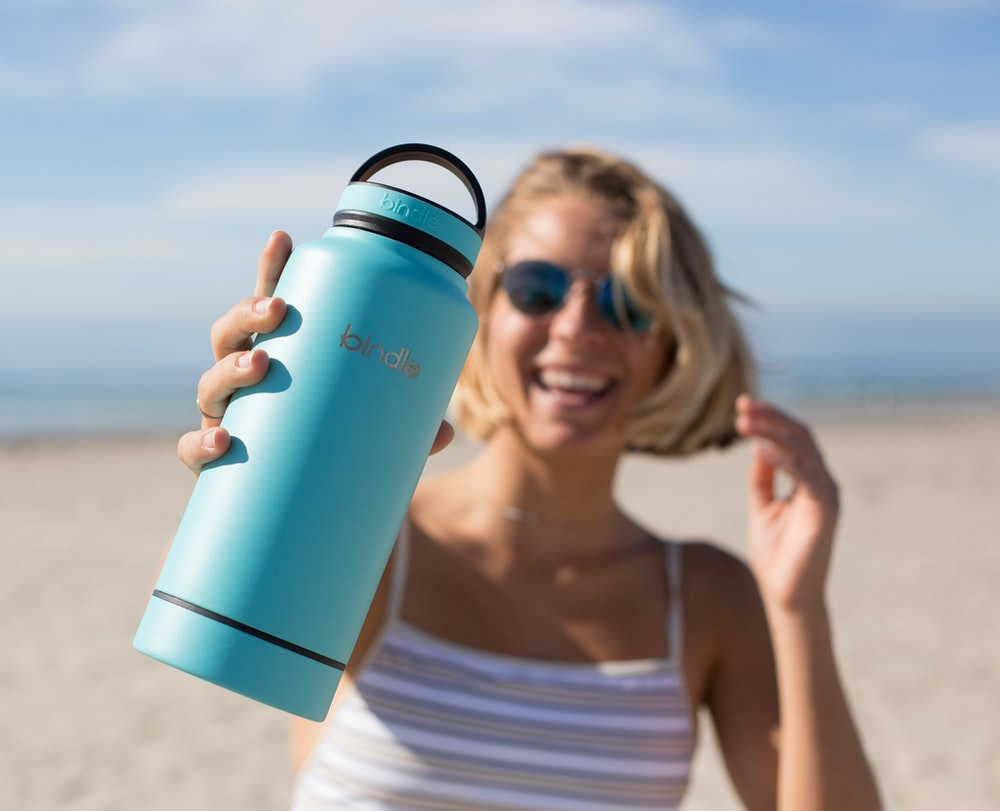 woman in white tank top holding blue and black tumbler