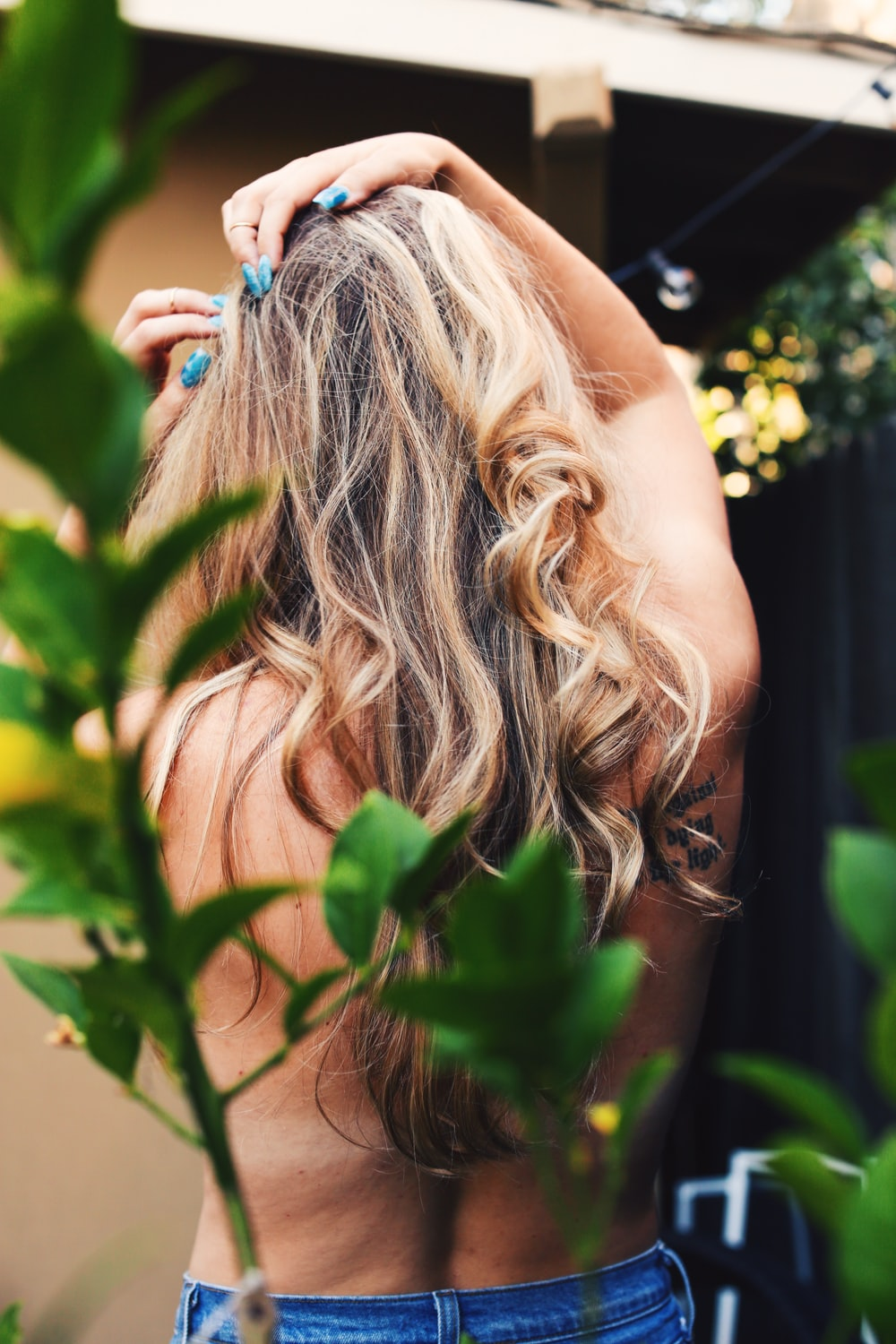 girl with blonde hair looking at green leaves