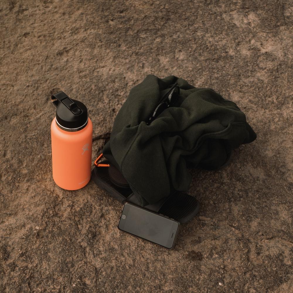 black smartphone beside orange and black tumbler
