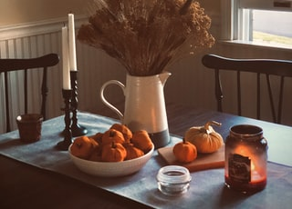 Some wheat grass and other dried fall foliage in a ceramic pitcher vase surrounded by taper candles, a bowl of tiny pumpkins and a lit Yankee candle. It is fall in New England!
