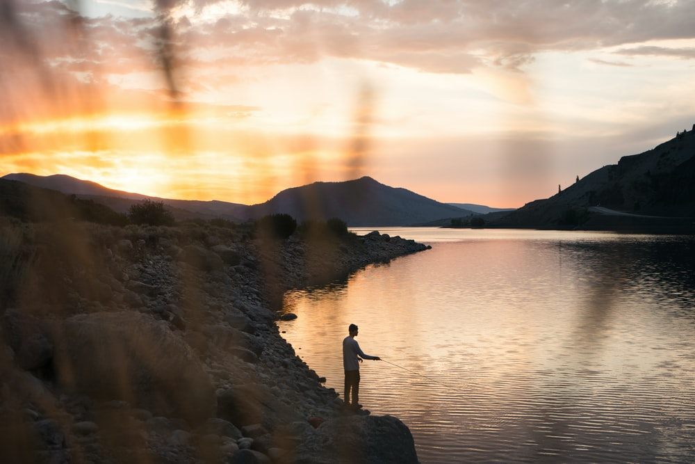 person standing on rock near body of water during sunset