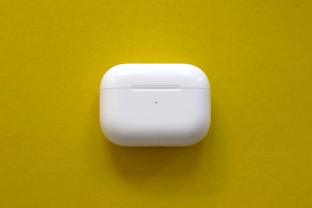 white apple charger on yellow surface