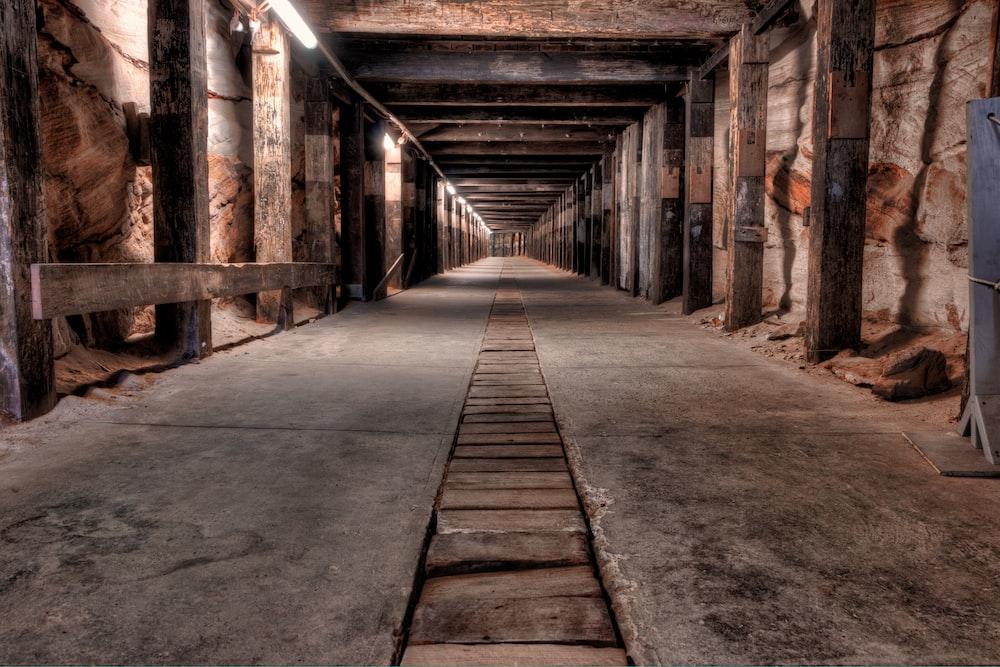 brown wooden pathway in between brick walls