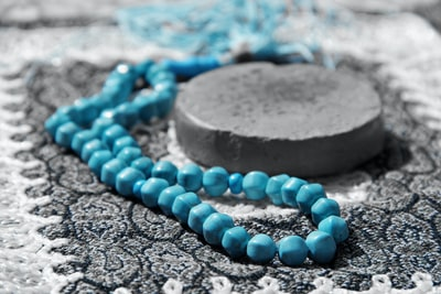 blue beaded bracelet on gray stone turquoise zoom background