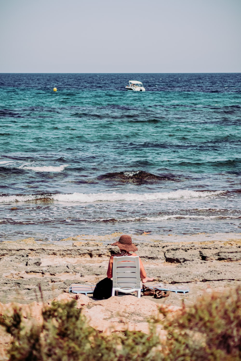 man in black shirt sitting on red and white surfboard on seashore during daytime