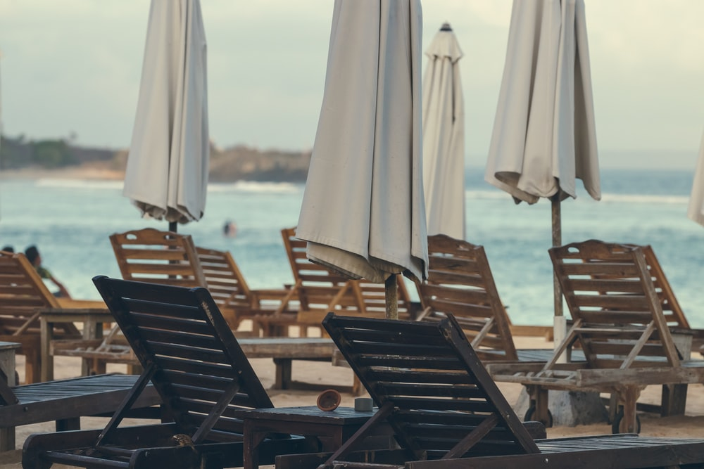 brown wooden chairs on beach during daytime