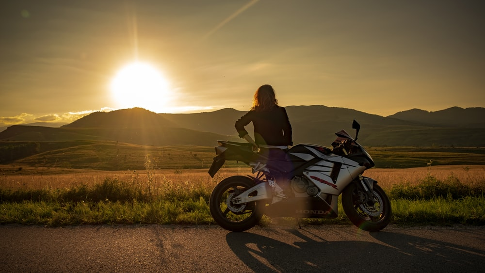 woman riding on black and white motorcycle during daytime