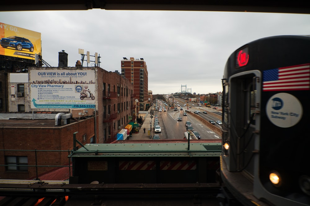 black train on rail road near city buildings during daytime