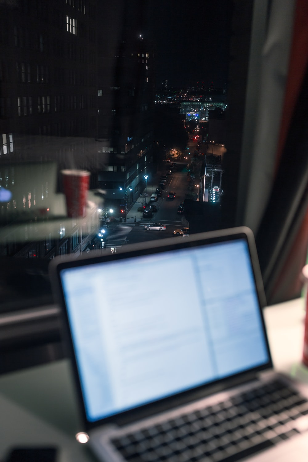 black laptop computer turned on near city buildings during night time