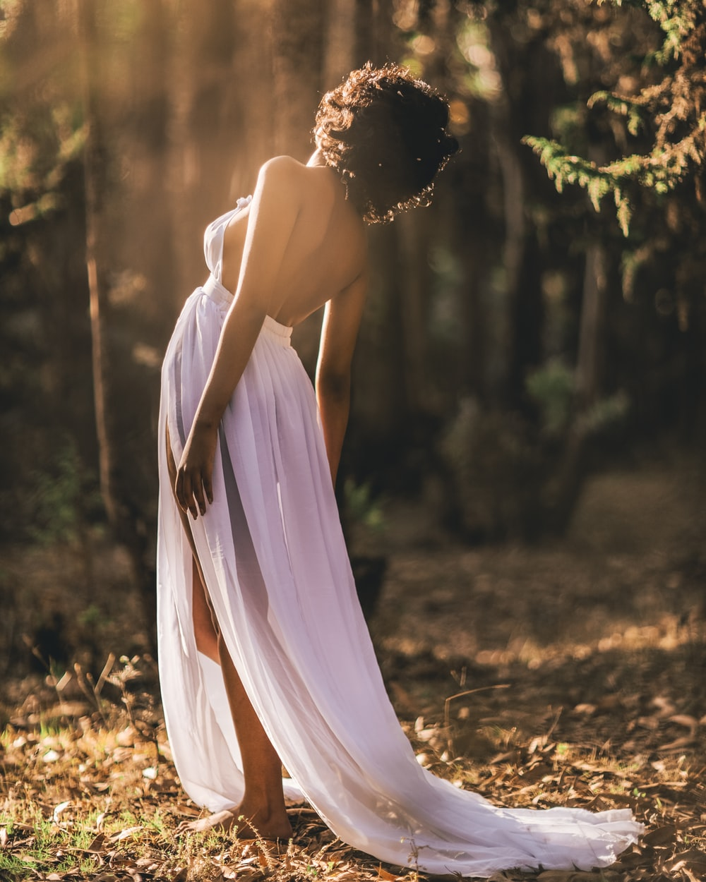 woman in white dress standing on brown dried leaves during daytime