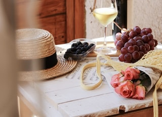 clear wine glass beside brown wooden round table
