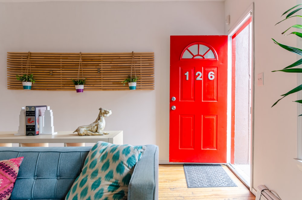 red wooden door near gray and white sofa
