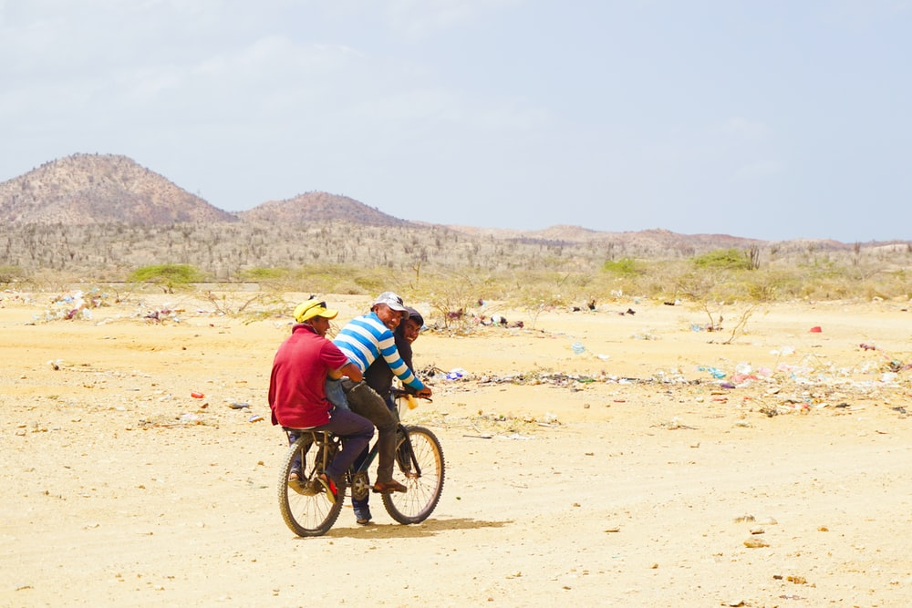 man in blue jacket riding bicycle on brown sand during daytime