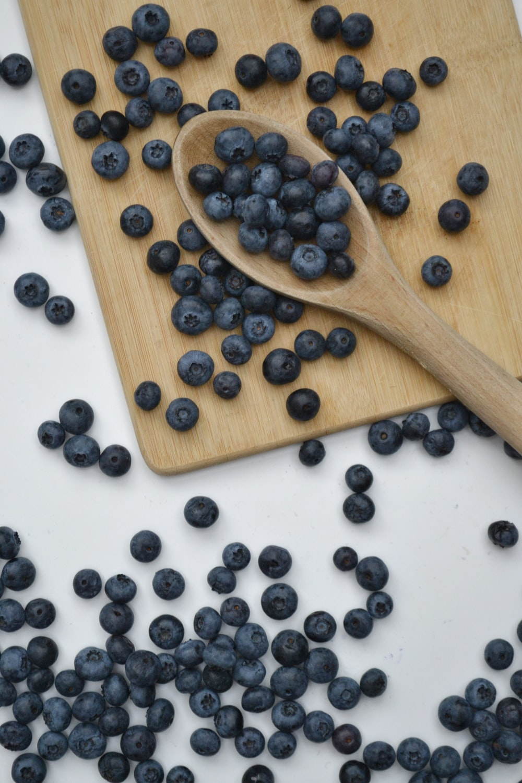 black berries on brown wooden spoon