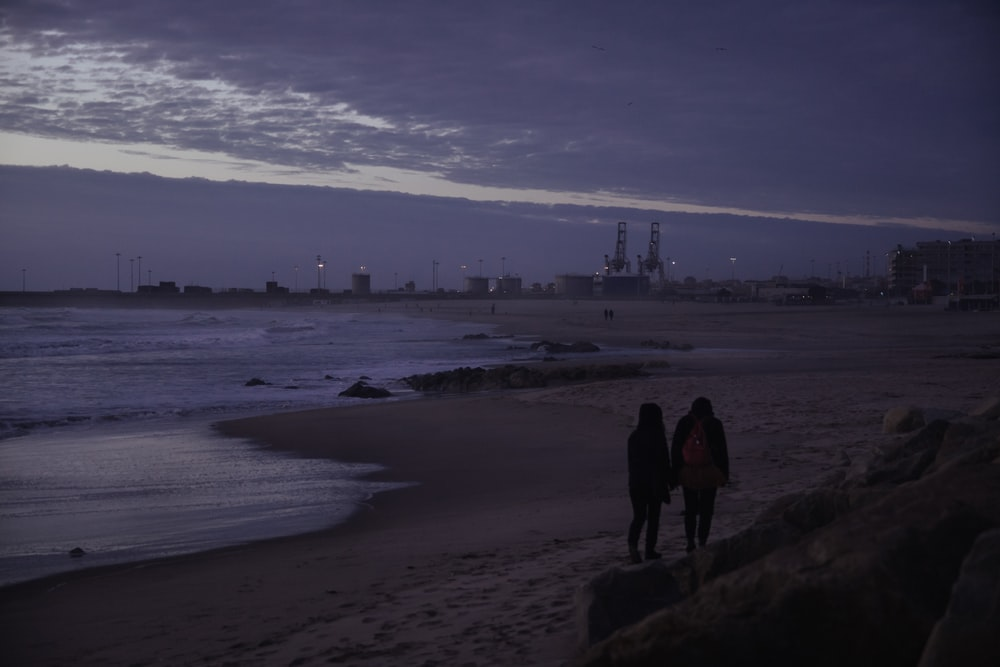 silhouette of man and woman standing on seashore during daytime