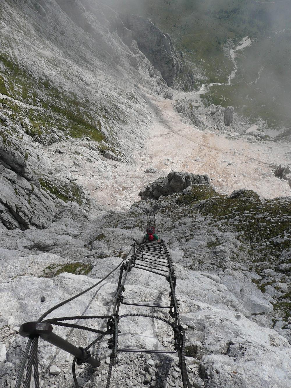 black metal ladder on rocky mountain