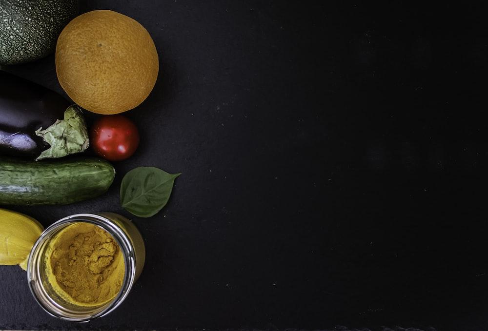 orange fruit beside green round fruit