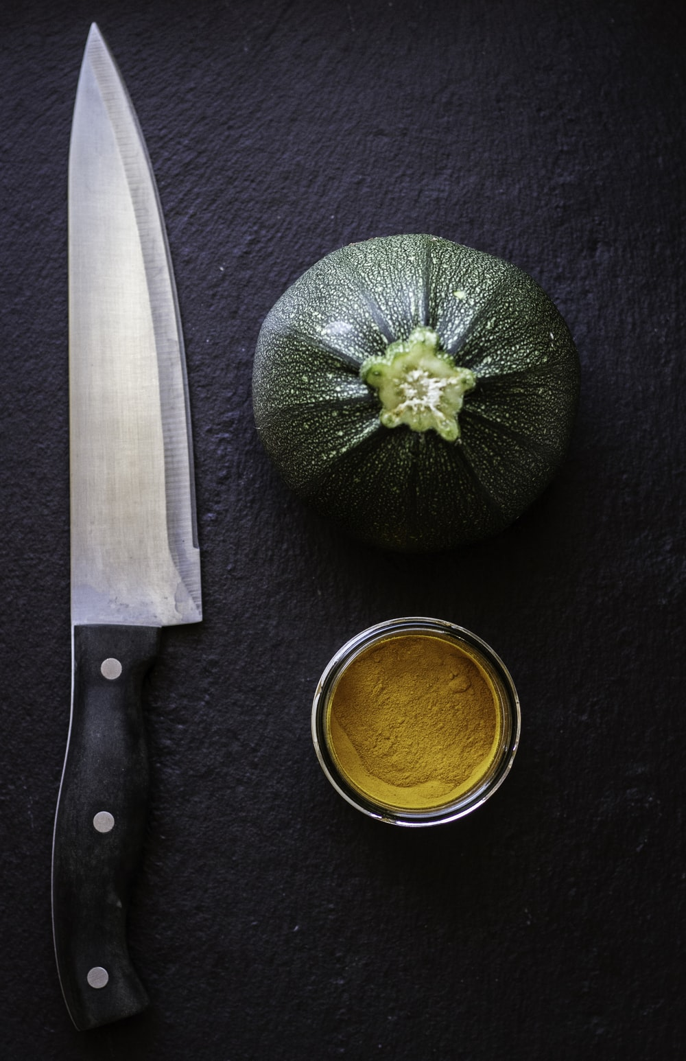 black handled knife beside green vegetable