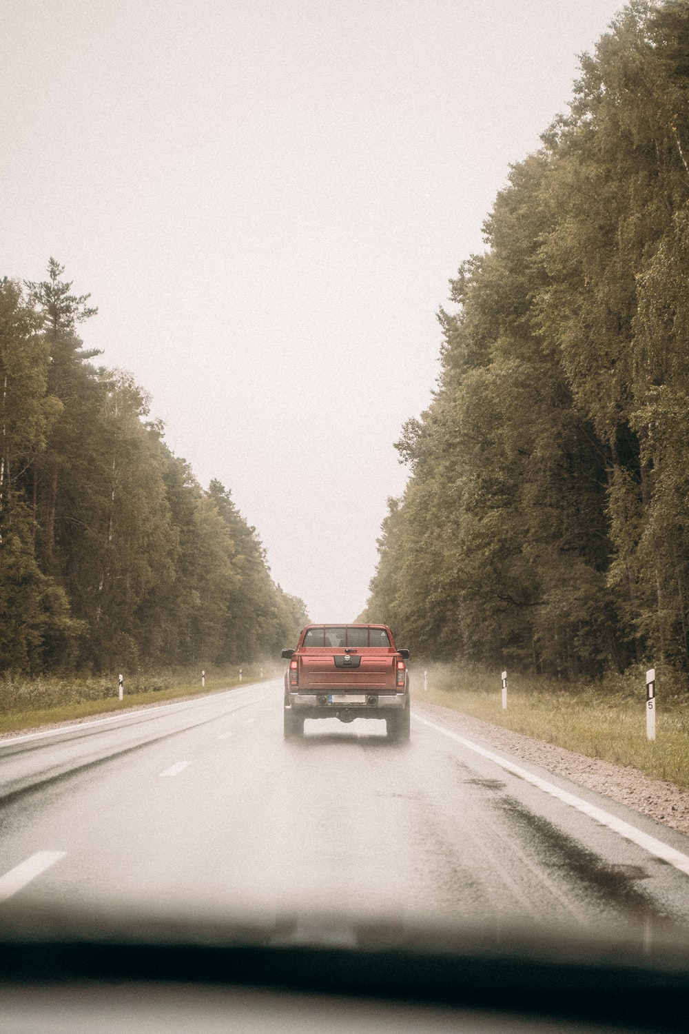 red suv on road between trees during daytime