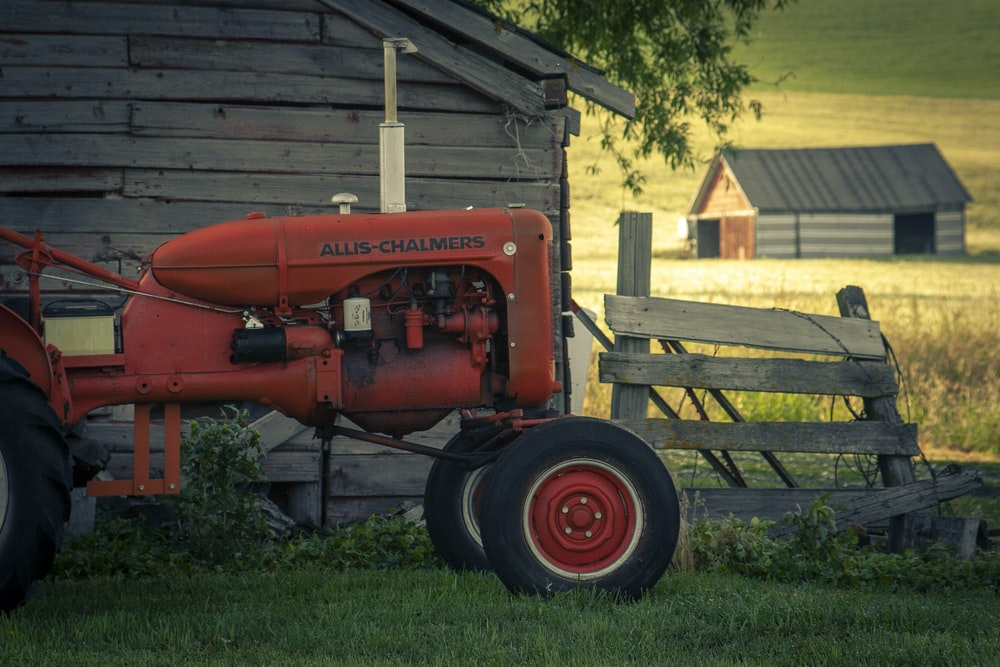 red tractor in front of brown wooden house