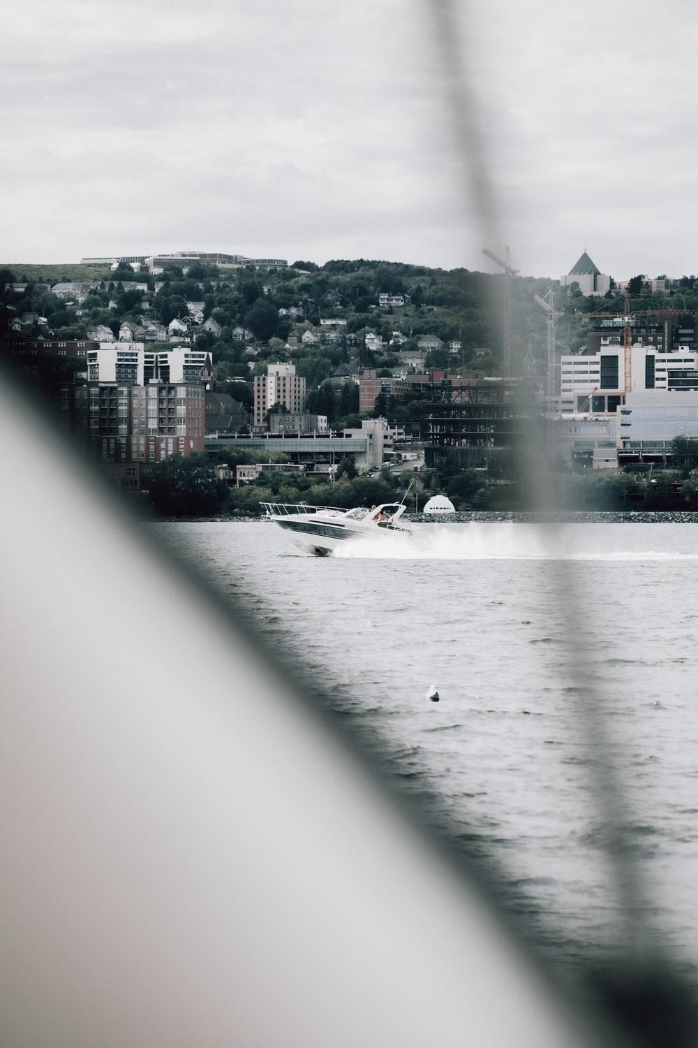 white boat on water near city buildings during daytime