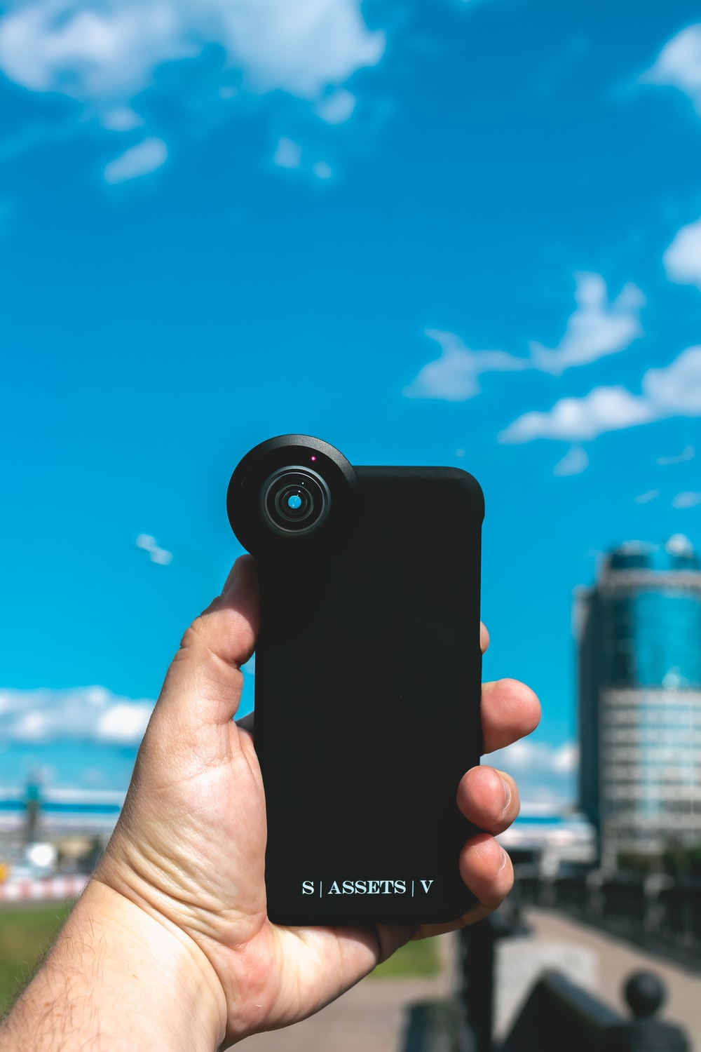 person holding black smartphone taking photo of city buildings during daytime