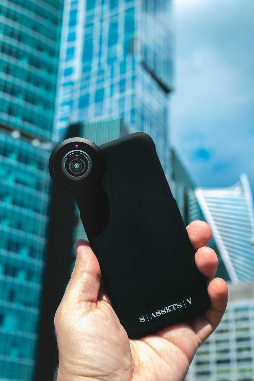 black canon camera lens in hand