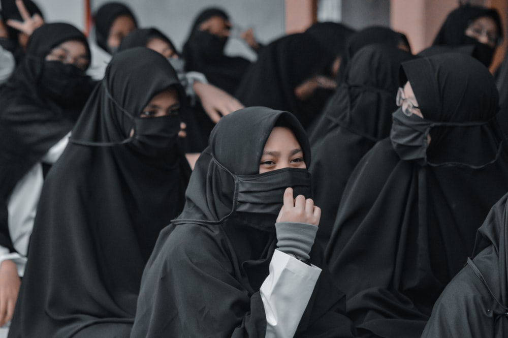 woman in black hijab holding white paper