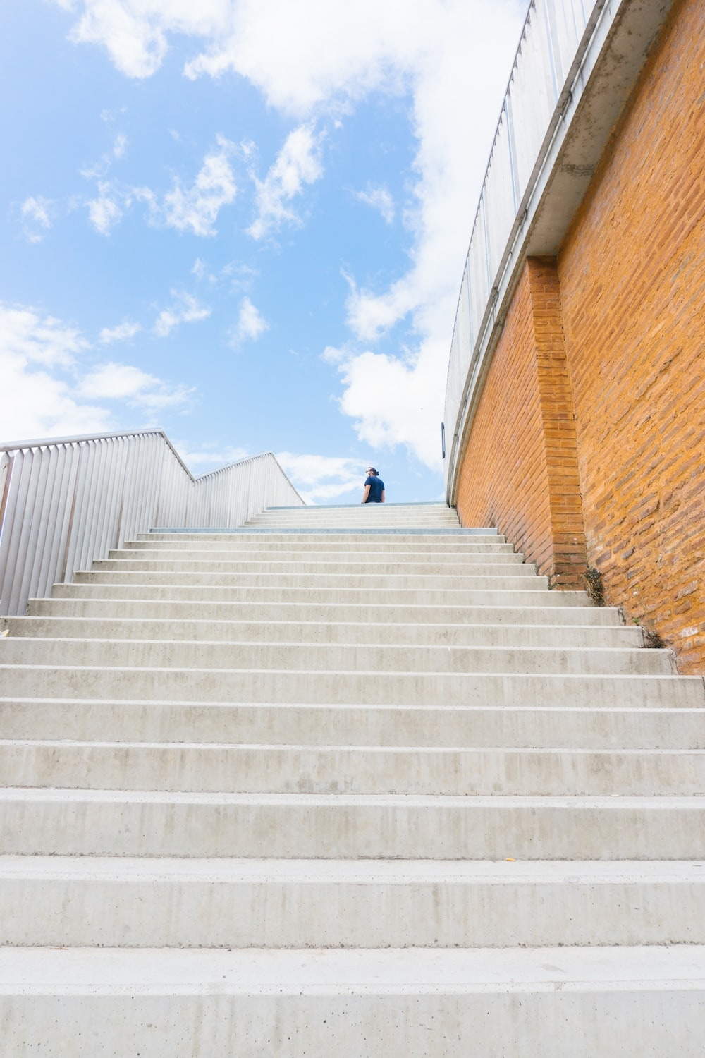 person in black jacket walking on white concrete stairs during daytime