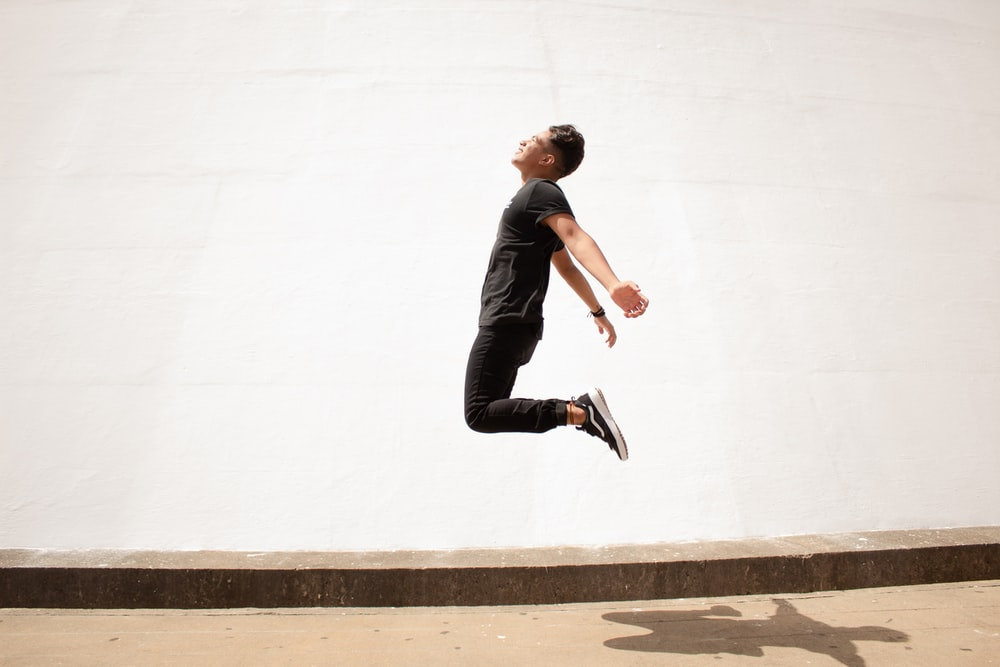 man in black jacket and black pants jumping on white concrete wall during daytime