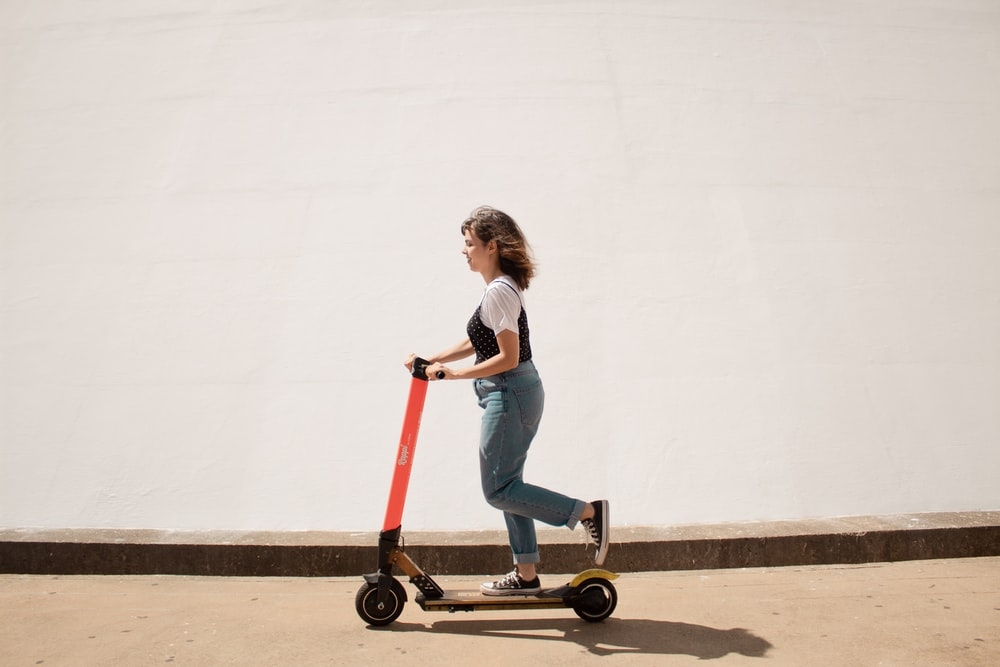 woman in white shirt and blue denim jeans riding red and black kick scooter