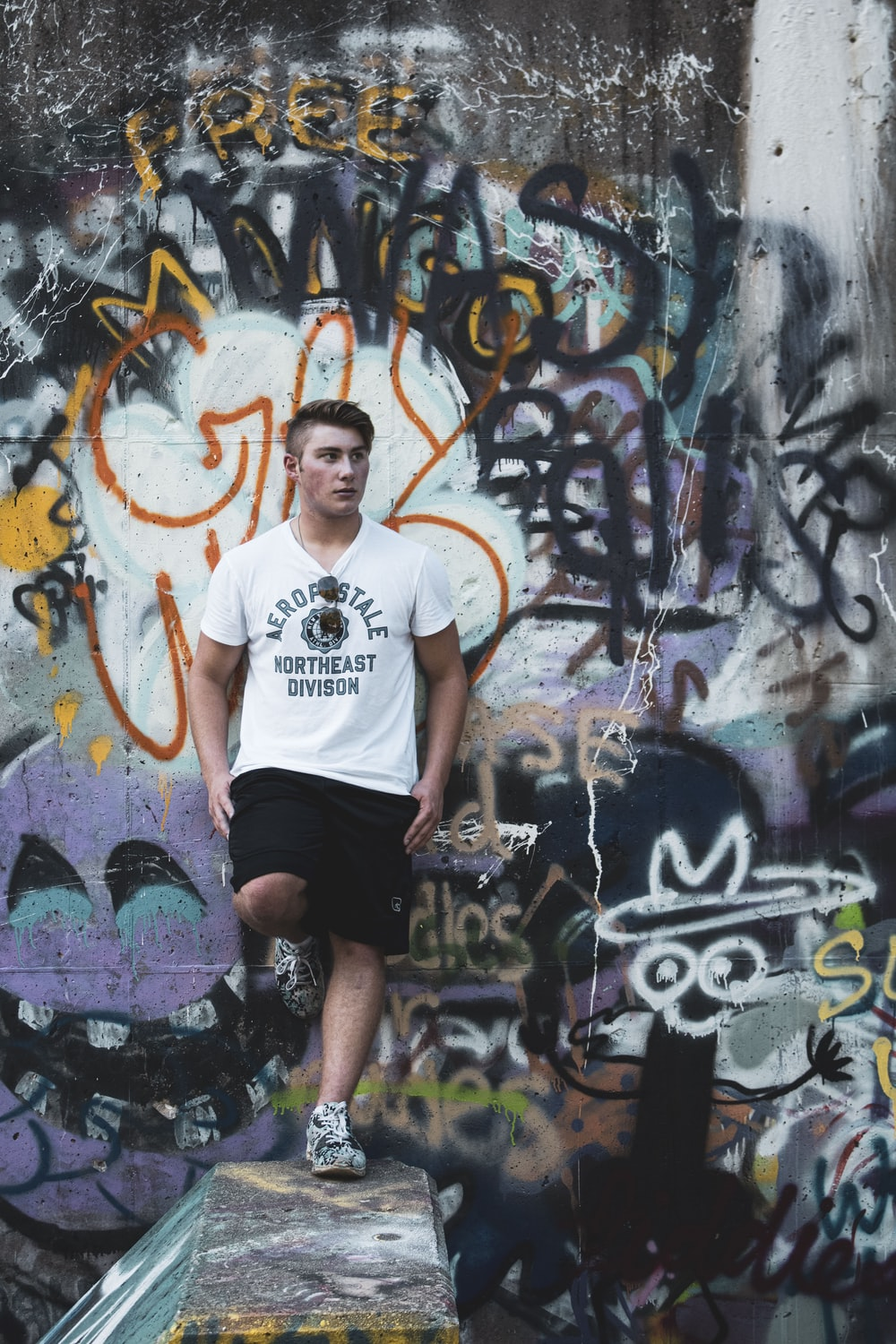 man in white crew neck t-shirt and black shorts standing beside graffiti wall