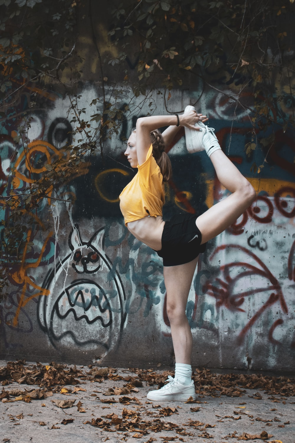 woman in yellow shirt and black shorts standing near wall with graffiti
