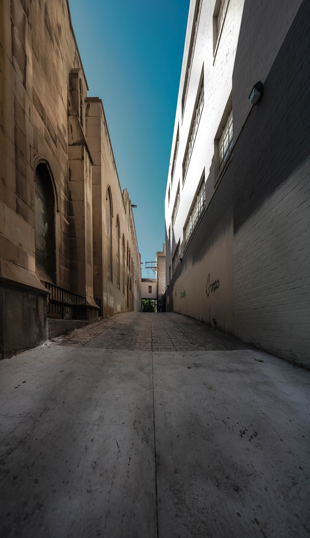 gray concrete pathway between brown concrete buildings during daytime
