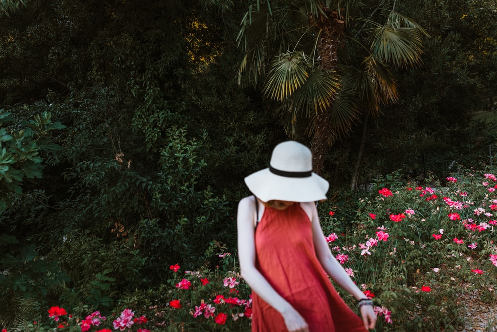 woman in red dress wearing white hat standing in front of green plants