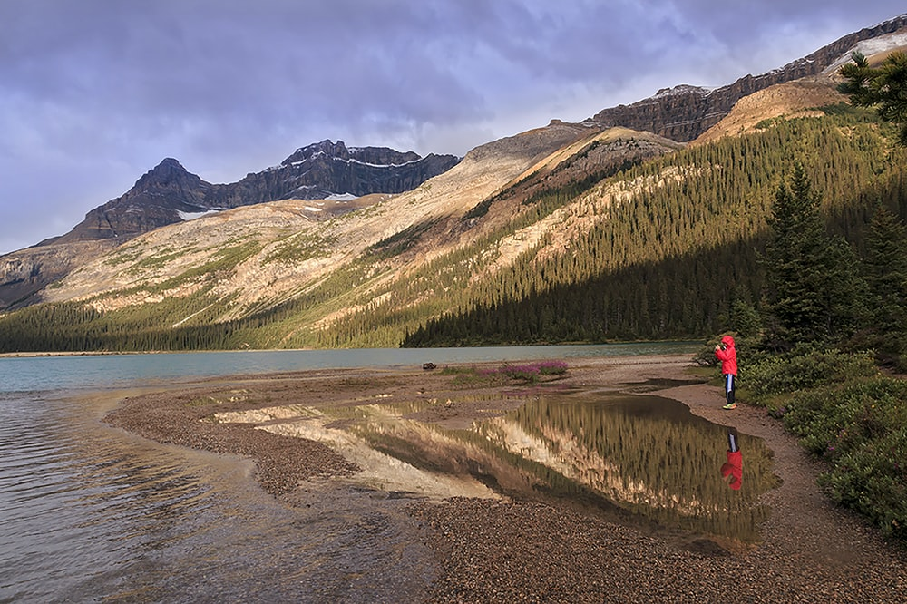 person in red jacket standing on brown sand near lake during daytime