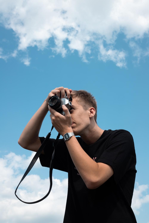 man in black crew neck t-shirt holding black dslr camera during daytime