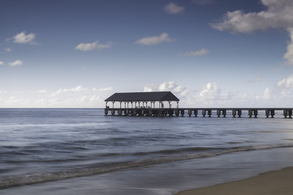 brown wooden house on beach during daytime