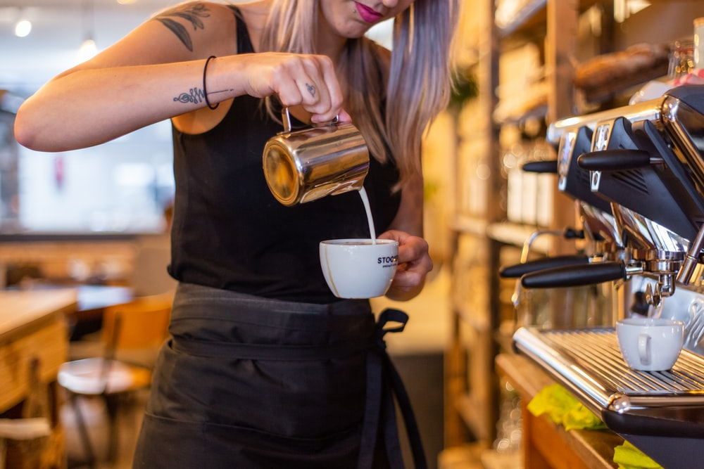 woman in black dress holding white ceramic mug