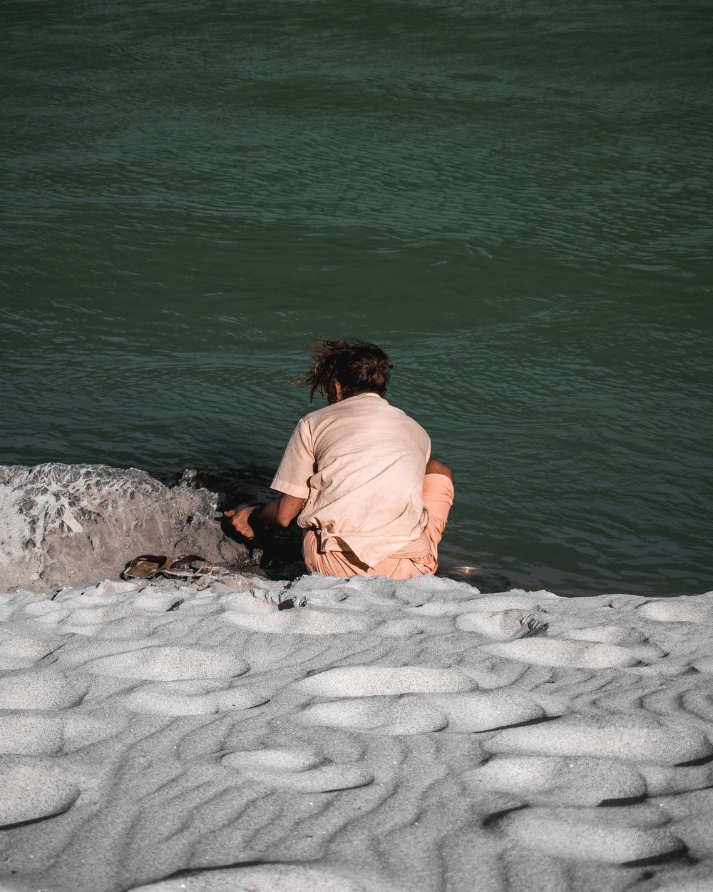 woman in brown shirt sitting on white sand near body of water during daytime