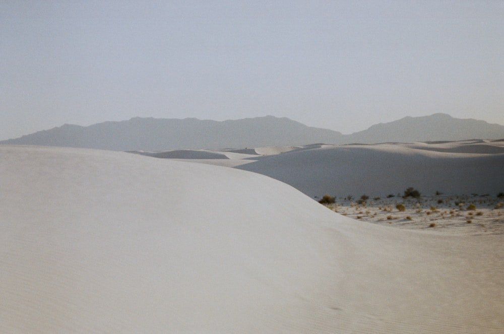 white sand with green grass and mountains in the distance