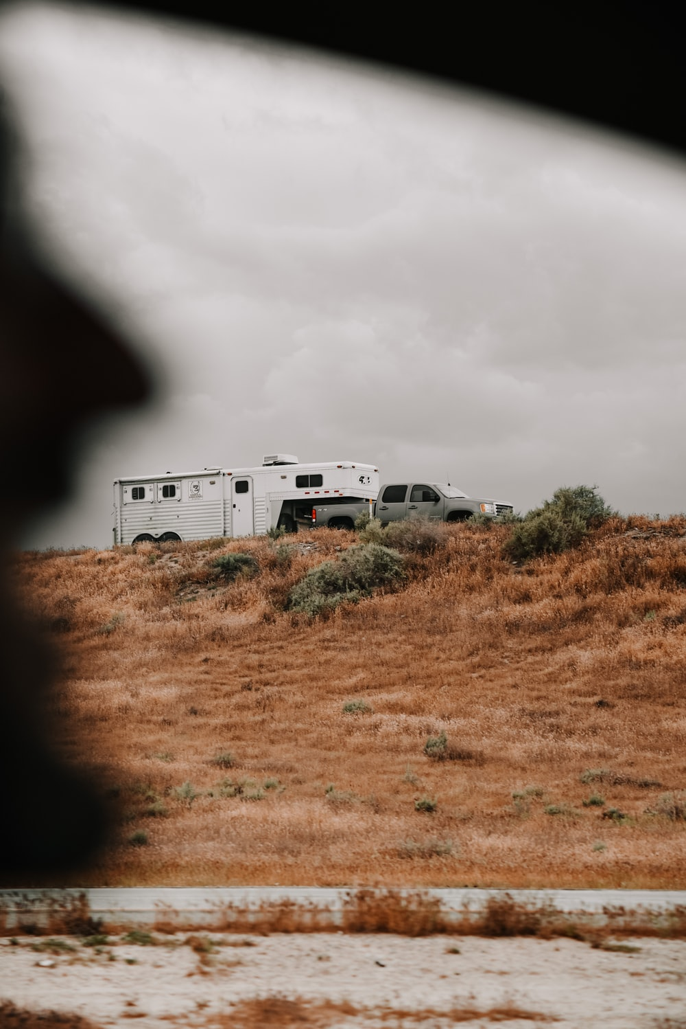 white rv trailer on brown grass field under gray cloudy sky during daytime